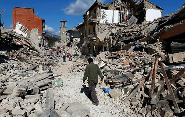 A man walks amidst rubble following an earthquake in Pescara del Tronto, central Italy, August 24, 2016. REUTERS/Remo Casilli